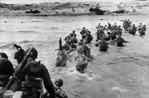 American troops landed on Normandy beaches (north-west of France), to come as reinforcements during the historic D-Day, 06 June 1944, during WW2. American troops supporting those already on the coast of Northern France, plunge into the surf and wade shoreward carrying equipment, on Utah Beach, Les Dunes de Madeleine, France. Bulldozers and other engineer equipment prepare the beach for the landing parties. AFP PHOTO STAFF (Photo credit should read STF/AFP/Getty Images)