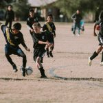 Soccer players dribbling the ball.