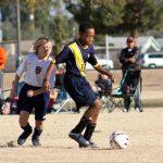 Soccer player dribbling ball.