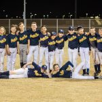 The baseball team are smiling for the photo.