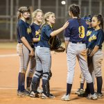 Some softball players are talking to each other.