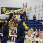 two volleyball girls jump at the net with arms outstreched above their head to block a spike from the other team