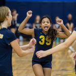 Two volleyball girls run towards another who was celebrating with her arms above her head
