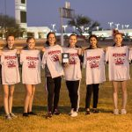 The girl's varsity cross country team smiling and posing for the photo while holding t-shirts.