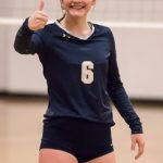 A female volleyball player is smiling and giving a thumbs up.