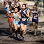 Multiple varsity cross country girls are racing each other during the event.