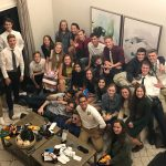 A group picture of the varsity cross country boys and girls at a living room.
