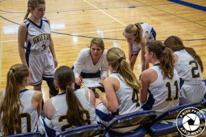 girls and coach in huddle at time out