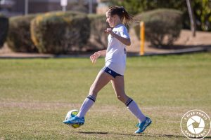 Girl dribbling soccer ball