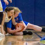 girls struggle for basketball on floor