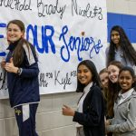 girls hanging banner on wall and smiling