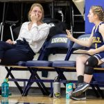 girl talks to coach and makes her laugh on bench