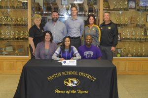 picture of Bria Garmon with her parents and coaches