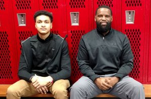Josiah Fulcher and Coach Quincey Simpson sitting in locker room.
