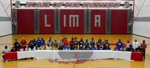 Athletes sit at a table in the gymnasium with their families during the signing ceremony.