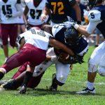 football player blocking ball carrier