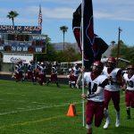 a team enters a stadium before a football game