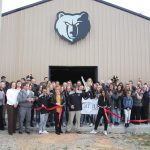 MJHS softball players, coaches and supporters cut the ribbon on the new indoor facility