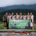 The MJHS girls soccer team grouped and smiling behind a banner after winning the Smoky Mountain Cup. The Smoky Mountains are in the background.