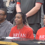 MJHS basketball player Nevaeh Majors sits at a long table with her family and coaches at her signing ceremony