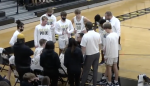 Distant view of the Golden Bears varsity basketball strategizing during a timeout
