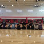 Volleyball players sitting on floor.