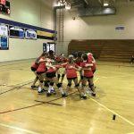 Volleyball team huddled together.