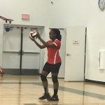 Volleyball player holding ball.
