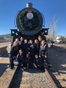 Basketball players in front of a train.