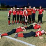 The softball team smiling,