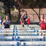Four girls race towards the camera over hurdles at a track event