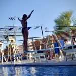 Girls on low diving board backwards with arms extended ready to dive