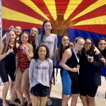Girls swim team holding second place medals in front of the Arizona flag