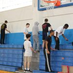 Freshman Basketball Players Help Spruce Up Middle School Gymnasium Over Break