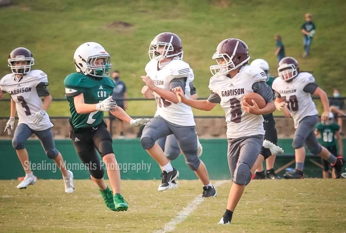 garrison player runs the ball against the crusaders