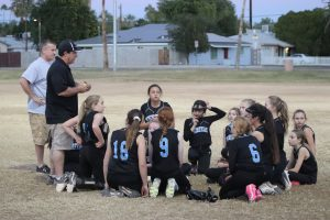 Coach talking to the softball players.