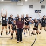 Volleyball team jumping for photo.