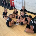 Volleyball players sitting on the floor.
