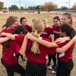 Softball team huddled together.