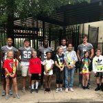 Varsity football players greet elementary school students in carpool