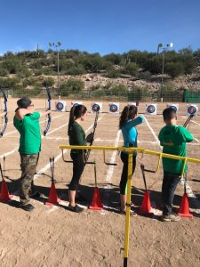 students with bows shooting arrows at targets