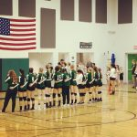 volleyball girls line up for national anthem in front of flag