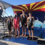 swim girls pose on podium in front of arizona flag