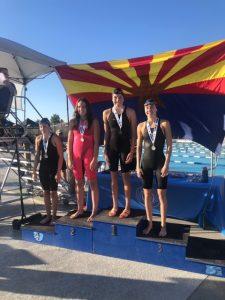 swim girls pose on podium in front of arizona flag