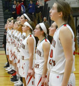 The varsity basketball team stands in a line during the National Anthem.