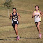 Two cross country girls running.