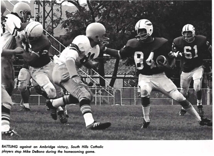 A black-and-white yearbook photo of a football player in a dark jersey holding a ball and reaching out toward a football player in a white jersey poised to spring. A caption reads,