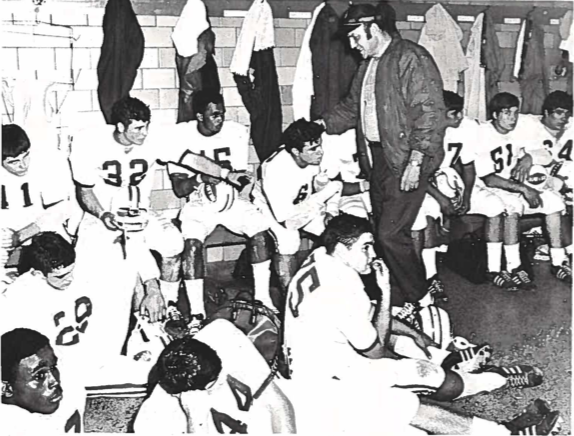 A black-and-white yearbook photo of a coach standing before a seated football team in white uniforms inside a locker room.