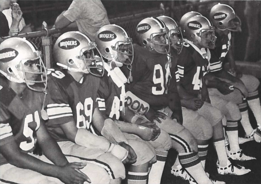 A black-and-white yearbook photo of seven football players, seated and all facing to the right. Their helmets display the word