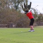 Golf player swinging his club.